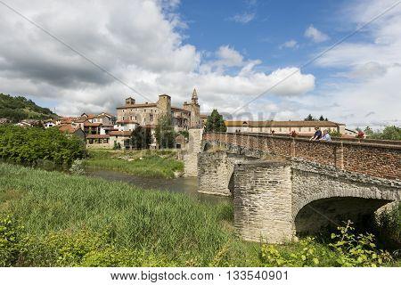Monastero Bormida Italy - May 29 2016: Bridge people river houses and Church of Monastero Bormida in Piedmont Italy