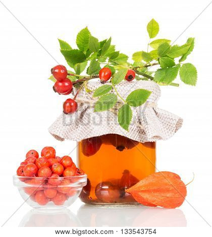 A bowl of berries of mountain ash, wild rose and fruktoy tea isolated on white background.