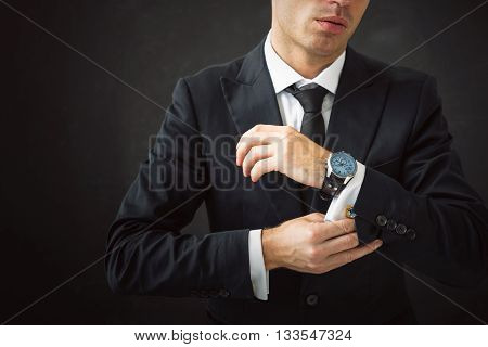 Business man fixing his shirt and cuff-links