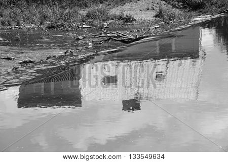 black and white photo of a house reflectiong on the water surface above the weir