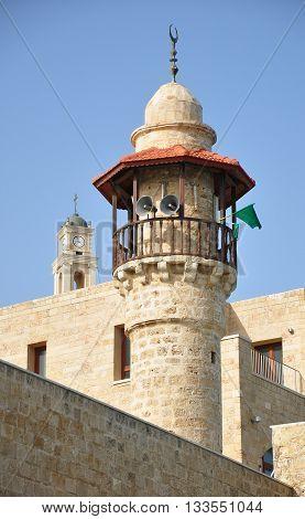 Minaret of old Jaffa mosque under blue sky. Israel.