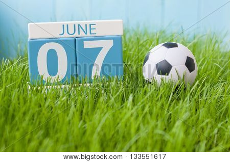 June 7th. Image of june 7 wooden color calendar on green grass background with football outfit. Summer day.