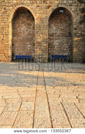 Ancient wall in Jaffa with alcoves for relaxation.