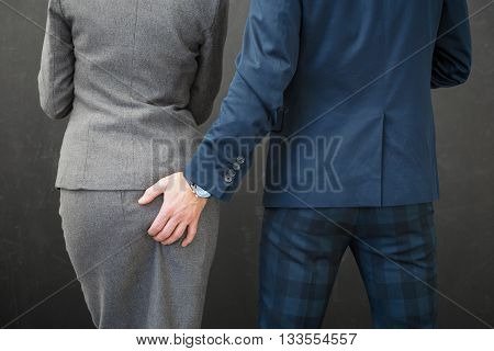 Co-worker touching woman's butt at the workplace