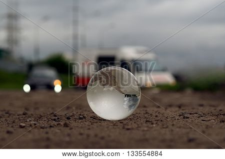 Transparent ball on the roadway. Evening lights of cars. In the bowl of a reflection of the electrical towers. Concepts, ideas - on the roads care. Electricity in the city. Urban ecology, traffic safety. Clean city