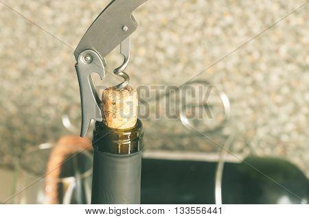 Steel corkscrew opens a bottle of wine closeup