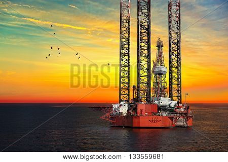 Oil drilling rig on sea at sunset.