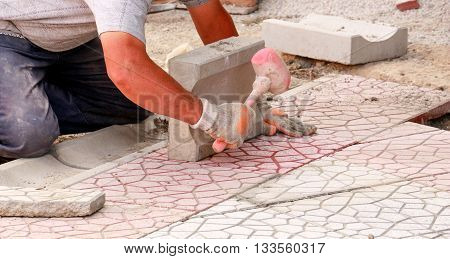 Workers tapping pavers into place with rubber mallets. Installation of granite paver blocks series with motion blur on hammers and hands.