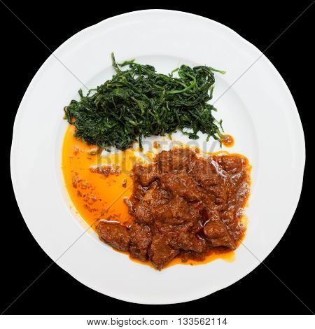Wild boar stew with hot sauce and spinach isolated on black