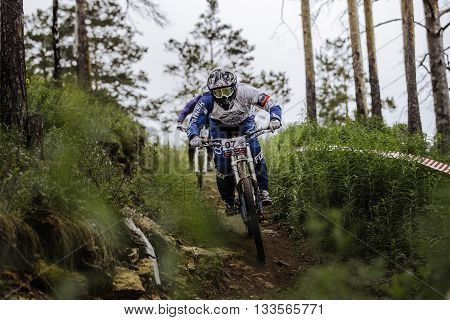 Miass Russia - May 29 2016: two athletes mountain bikers descend mountain track during Cup