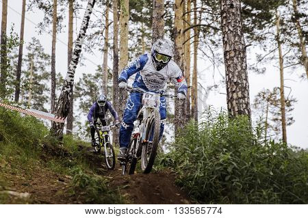 Miass Russia - May 29 2016: rivalry between two athletes mountain bikers on track during Cup