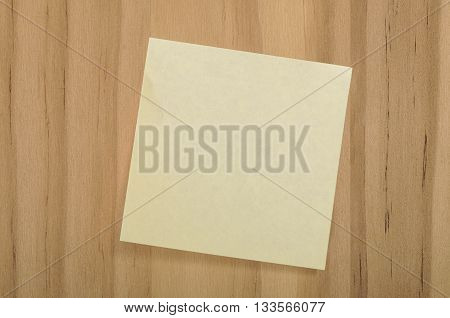 Blank Yellow Square Sticky Note on Wood Background for Your Copy