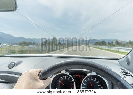 Hand of a driver on the steering wheel on a highway on a partly cloudy day with the alp in the far background