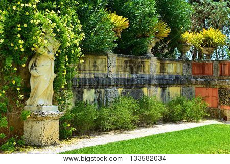 Rustic style wall surrounded with lush green tropical plants taken in a garden