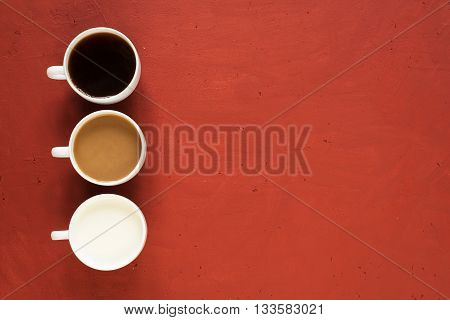 Three cups with black coffee, milk coffee and just milk on red background.