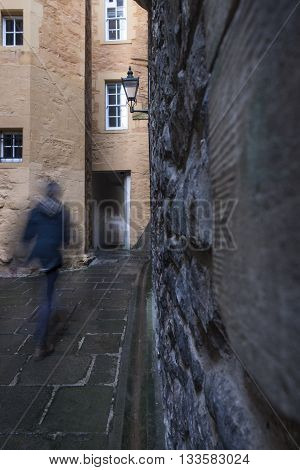 Motion blur as a man walks through one of the many narrow closes (lane) off the Royal Mile in Edinburgh Scotland