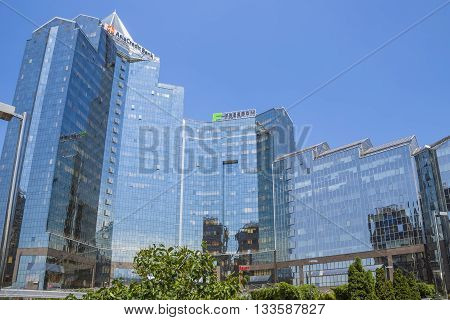 ALMATY KAZAKHSTAN - JUNE 8 2016: Business Center Nurly Tau in Almaty Kazakhstan. Made in the style of Hi-Tech repeating silhouettes of mountains Zailisky Alatau. Construction company - Basis A.