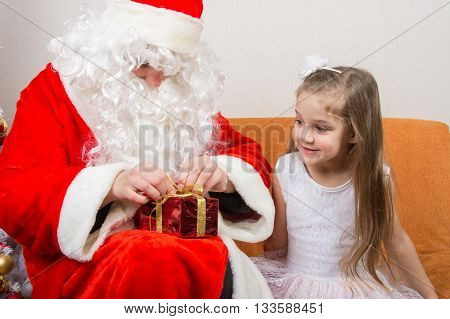 Santa Claus Helps To Untie The Ribbon Gift, Little Girl Happily Looking At Him