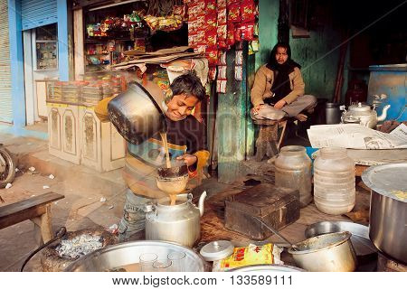 VARANASI, INDIA - JAN 5, 2016: Unidentified happy kid helping to pour the tea-masala in a roadside cafe on poor indian street on January 5, 2016. Varanasi urban agglomeration had population of 1435113