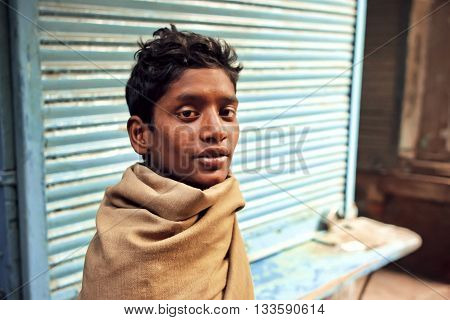 VARANASI, INDIA - JAN 5, 2016: Portrait of young poor homeless man on abandoned street of indian city with closed stores on January 5, 2016. Varanasi urban agglomeration had popul. of 1435113