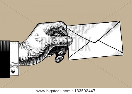 Hand with a Postal envelope. Hand with a mail. Retro style mail sign and icon. Vintage engraving stylized drawing