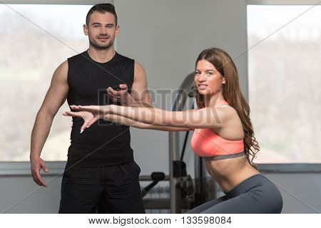 Woman With Personal Trainer Train On Bosu Ball