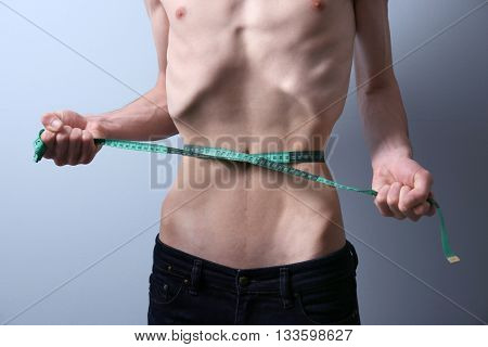 Young man measuring himself on grey background