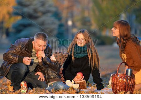 Happy family resting in a park in autumn. Family sitting in the yellow autumn leaves. Cheerful family relaxing in the park in autumn. Kid eating an apple in the park in autumn.
