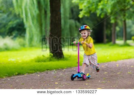 Little child learning to ride a scooter in a city park on sunny summer day. Cute preschooler boy in safety helmet riding a roller. Kids play outdoors. Active leisure and outdoor sport for children.