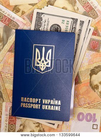 International Ukrainian passport with US dollars on Hryvna banknotes background