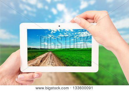 tablet computer isolated in a hand on the nature backgrounds