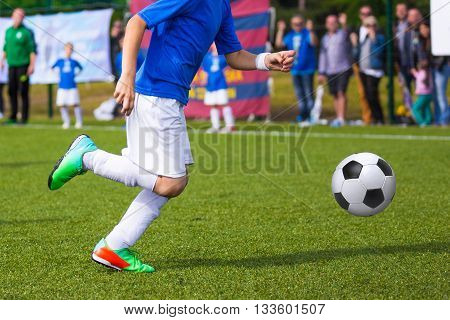 Boy kicking soccer ball on sports field. Soccer football training session for children teens