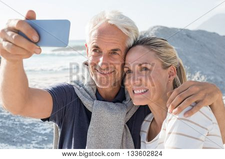 Happy romantic couple embracing on the beach and taking a photo with smart phone. Portrait of senior smiling couple taking a selfie in a summer vacation at sea. Happy mature couple take a picture.