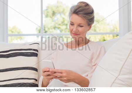 Senior woman using mobile phone while sitting on sofa. Older woman sitting on sofa and texting a phone message. Portrait of a beautiful elderly woman learning to use smartphone. poster