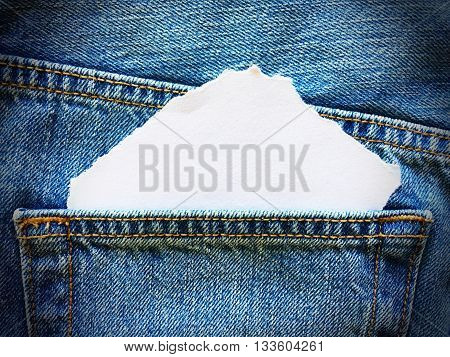 white paper in the pocket of blue denim jeans
