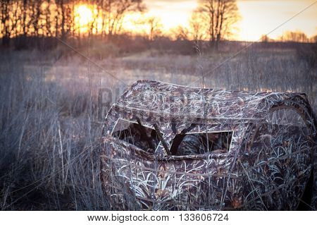 hunters waiting for prey in hunting tent in reed bushes next to the river during sunrises. Gun barrels  stick out from tent window