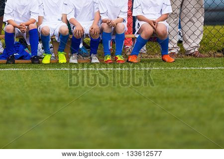 Group Of Children In Soccer Team Having Training. Youth Young Soccer Football Team on a Soccer Sport Field. Group of Boys Soccer Players Sitting Together and Supporting Team. Young reserve players on a soccer bench.
