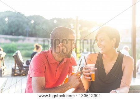 Couple Having A Cocktail Outdoor At Sunset