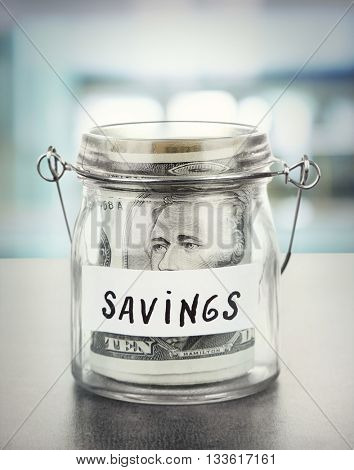 Jar for savings full of banknotes on bright background