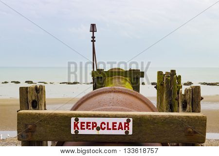 A rusty water pipe on the beach of Hastings.