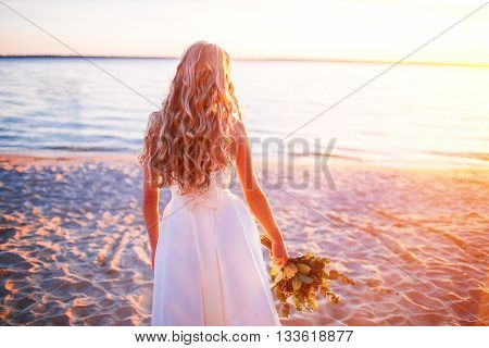 Bride in wedding dress at the beach at sunset