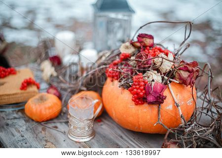 halloween inspiration. Autumn still life. pumpkin, dry roses, viburnum honey cake. Honey in a vase. dry twigs. on the table