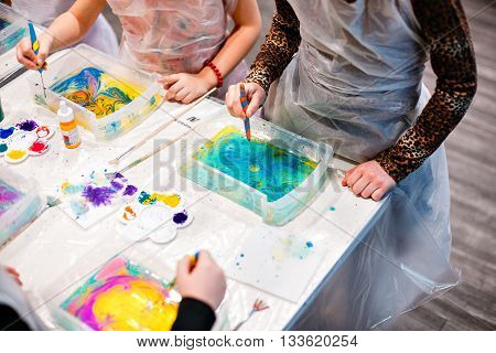 Child drawing with needle on the water. Ebru art is a method of aqueous surface design.