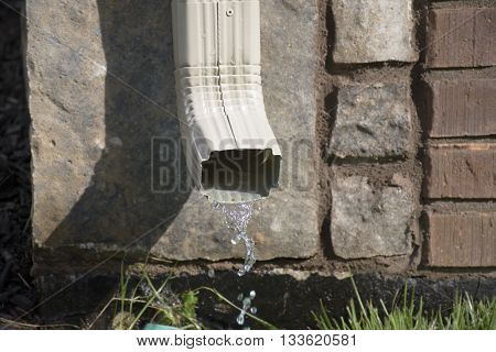 A rain gutter downspout with water coming out with stones and bricks in the background. Shallow Depth of Field.