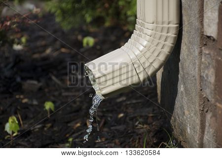 A rain gutter downspout with water coming out from the side with a flower bed in the background. Shallow Depth of Field.