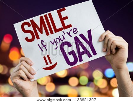 Smile If You're Gay placard with night lights on background