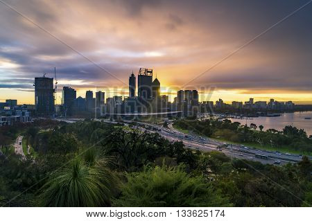 The sun rises behind the city skyline of Perth, Western Australia.