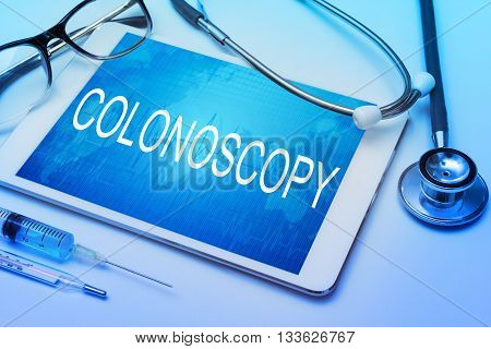 Colonoscopy word on tablet screen with medical equipment on background
