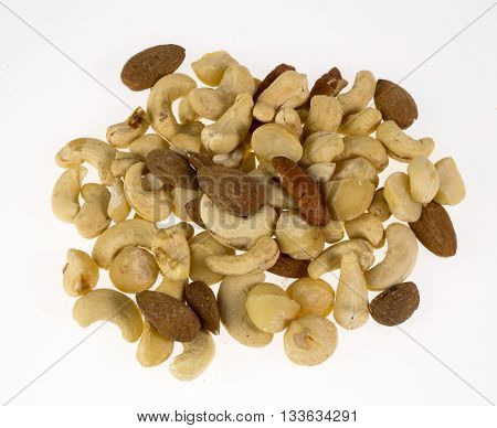 Mixed exotic nuts on a white background in a heap.