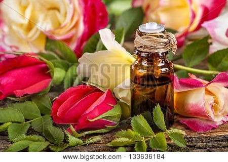 Essential oil made from roses on a rustic table
